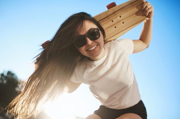 Tiro de ángulo bajo chica patinadora despreocupada con cabello largo oscuro, flexión