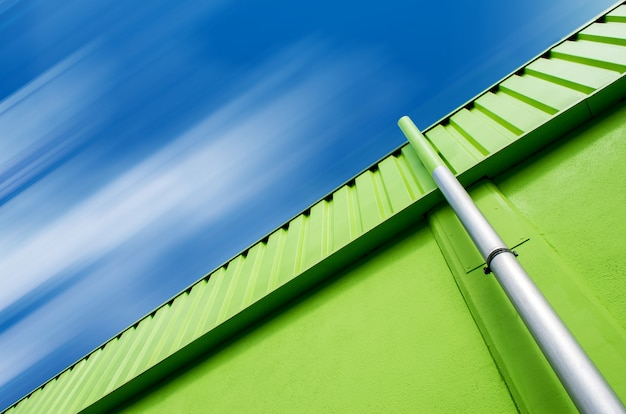 Tiro de ángulo bajo de un edificio verde con un tubo gris bajo el cielo nublado