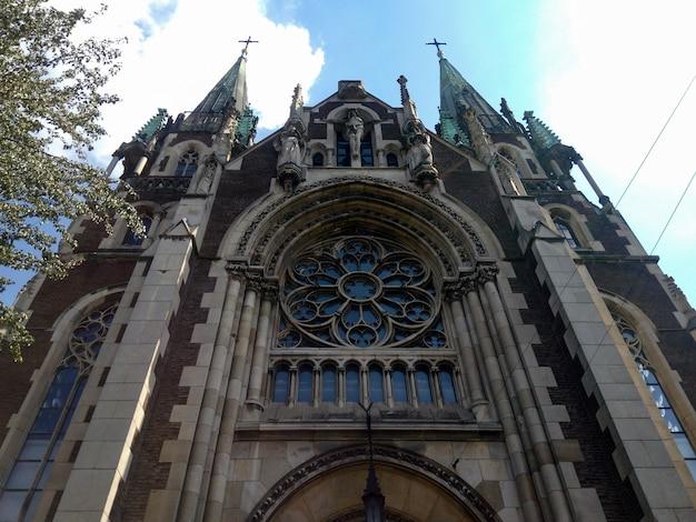 Tiro de ángulo bajo exterior de una hermosa catedral con nubes en el cielo azul