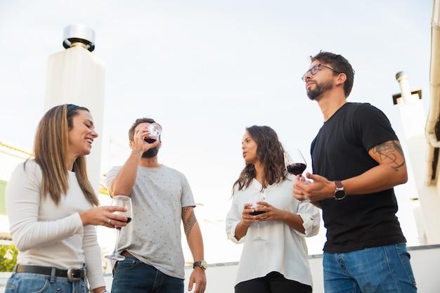 Tiro de ángulo bajo de gente sonriente bebiendo vino tinto y hablando
