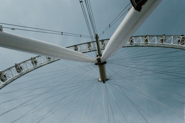Tiro de ángulo bajo de una gran rueda de la fortuna bajo el cielo azul claro