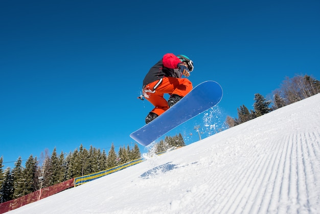 Tiro de ángulo bajo del hombre snowboarder saltando en el aire mientras practica snowboard