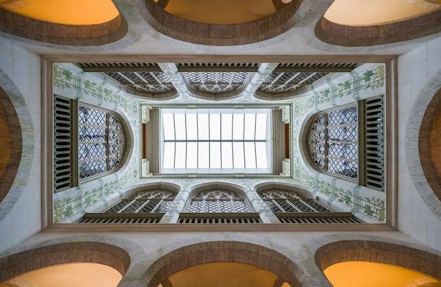 Tiro de ángulo bajo del interior de un antiguo edificio con paredes geométricas y cúpulas.