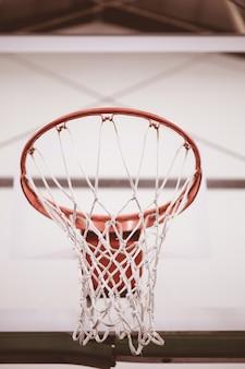Tiro de ángulo bajo de primer plano de la red de baloncesto en la cancha de baloncesto