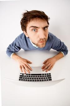 Tiro de ángulo superior de ojo de pez del joven pensativo y sospechoso que tiene dudas, mira con incredulidad, trabaja con la computadora portátil