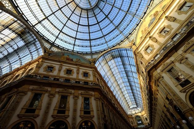 Tiro de ángulo bajo de techo de cristal con paredes blancas y doradas con imágenes