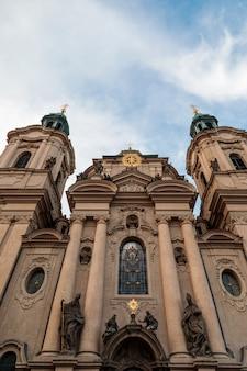 Tiro de ángulo bajo vertical de la iglesia de san nicolás bajo el cielo nublado en praga, república checa