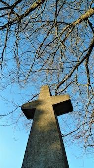 Tiro de ángulo bajo vertical de piedra hecha estatua cruzada con ramas y cielo despejado