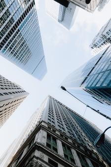 Tiro de ángulo bajo vertical de los rascacielos bajo el cielo brillante en la ciudad de nueva york, estados unidos