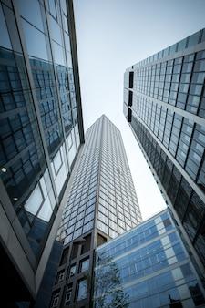 Tiro de ángulo bajo vertical de rascacielos de gran altura en una fachada de vidrio en frankfurt, alemania