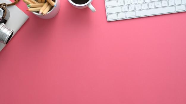 Tiro de arriba del espacio de trabajo del diseñador con la computadora en la mesa rosa