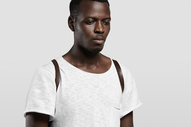 Tiro en la cabeza interior de un estudiante de piel oscura de buen aspecto vestido con una camiseta blanca en blanco y una mochila de cuero que se encuentran aisladas contra la pared de hormigón