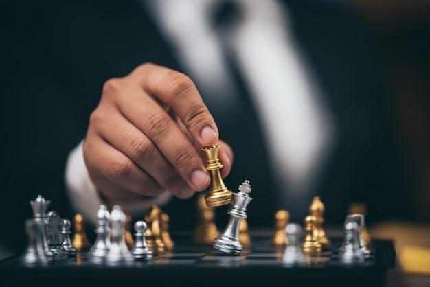 Tiro de cerca ajedrez dorado para derrotar al ajedrez asesino del rey de plata en el tablero de ajedrez blanco y negro para el concepto de ganador y perdedor de la competencia de desafío comercial