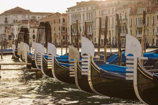 Tiro cercano de barcos cerca del muelle en el agua con edificios borrosos en el fondo durante el día
