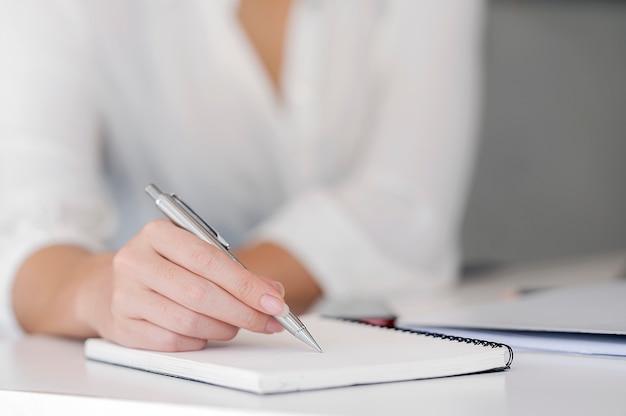 Tiro cercano de una mano femenina que escribe algo en el cuaderno en el primero plano.