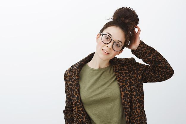 Tiro de cintura para arriba de la atractiva chica caucásica moderna con elegantes gafas negras y abrigo de leopardo sobre camiseta casual, tocando el cabello, inclinando la cabeza