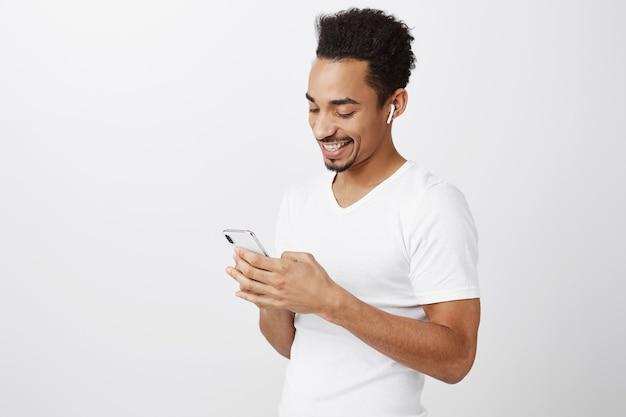 Tiro de cintura para arriba de atractivo hombre afroamericano charlando, enviando mensajes de texto a un amigo, escuchando música o viendo videos en auriculares inalámbricos