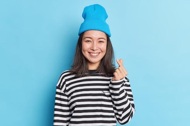 Tiro de cintura para arriba de bonita mujer asiática con cabello oscuro hace corazón coreano con los dedos lleva sombrero puente rayado sonríe agradablemente