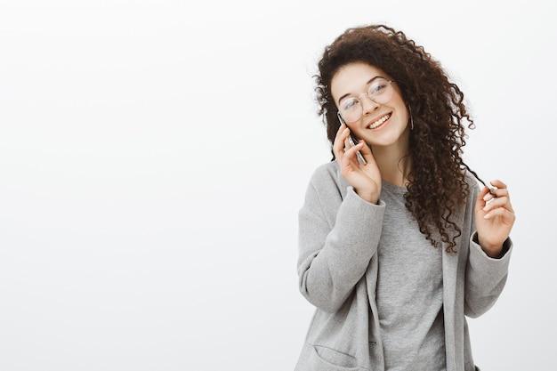 Tiro de cintura para arriba de una chica elegante y amigable saliente con cabello rizado en elegantes gafas y abrigo gris, hablando por teléfono inteligente, inclinando la cabeza y sonriendo ampliamente