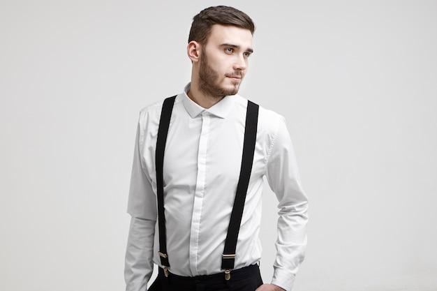 Tiro de cintura para arriba de chico guapo de moda con elegante barba de pie en la pared blanca del estudio con aspecto positivo de ensueño, vestido con elegante camisa blanca con tirantes. concepto de personas y estilo de vida