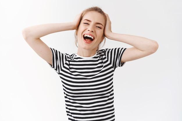 Tiro de cintura para arriba, despreocupada, vivaz mujer joven emotiva con moño desordenado en camiseta a rayas, sonriendo cantando y disfrutando de un hermoso día, sintiéndose relajado y encantado, tocando la cabeza bailando, fondo blanco