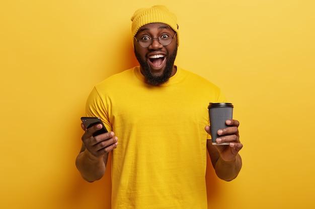 Tiro de cintura para arriba de hipster étnico feliz desarrolla un sitio web personal en un teléfono celular, conectado a internet inalámbrico, sostiene una taza desechable de bebida caliente, tiene una barba gruesa, usa un sombrero amarillo y una camiseta