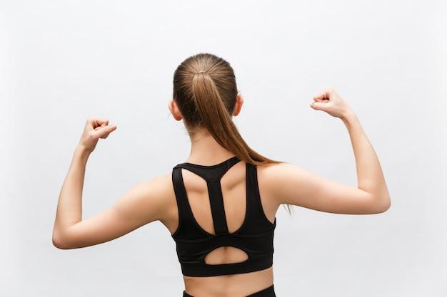 Tiro de cintura para arriba de mujer deportiva levanta la mano para mostrar sus músculos