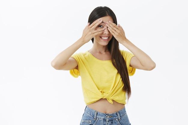 Tiro de cintura para arriba de la mujer europea linda intrigada y alegre creativa en la camiseta amarilla de moda que cubre los ojos con las palmas