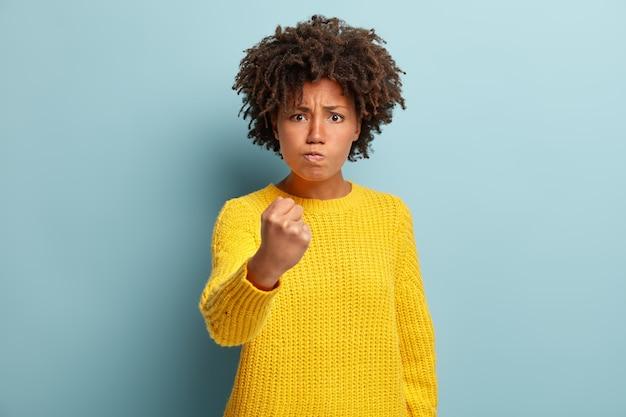 Tiro de cintura para arriba de mujer de piel oscura insatisfecha hosca tiene peinado afro, agita el puño y mira con amenaza