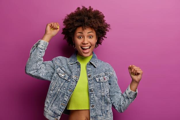 Tiro de cintura para arriba de optimista alegre mujer afroamericana levanta la mano, se siente optimista, se mueve felizmente, aprieta los puños, usa chaqueta de mezclilla, aislada sobre una pared vibrante púrpura. concepto de estilo de vida feliz
