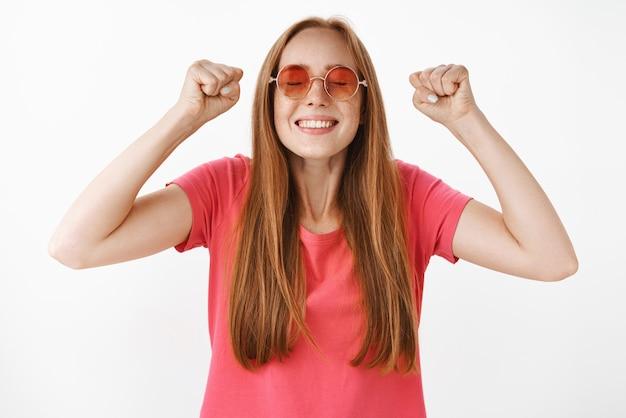 Tiro de cintura para arriba para triunfar, feliz y emotiva, complacida joven pelirroja con pecas en gafas de sol y camiseta casual rosa levantando los puños cerrados en la victoria celebrando el exitoso final del semestre