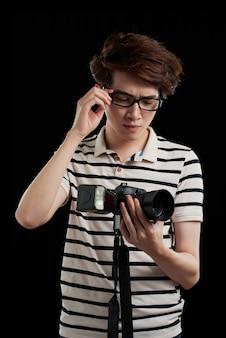 Tiro de la cintura del fotógrafo asiático contra el fondo negro mirando a su cámara con expresión de la cara decepcionada