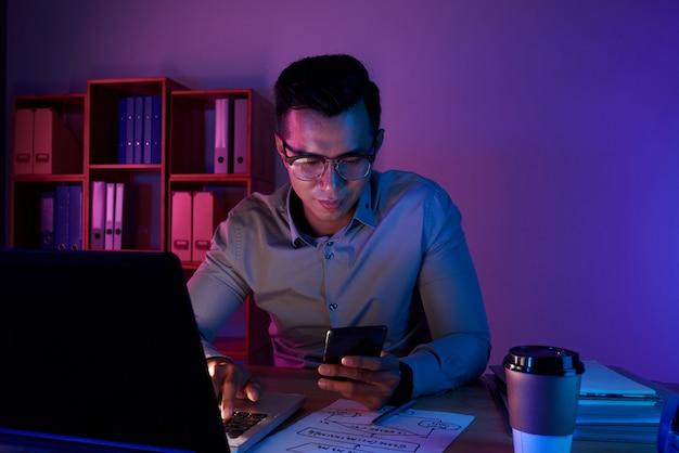 Tiro de la cintura del hombre trabajando hasta tarde en la computadora