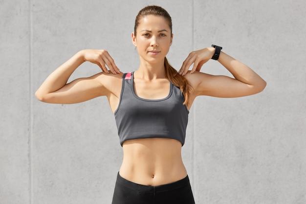 Tiro en la cintura de una joven atleta atractiva, se calienta antes de trotar, mantiene las manos sobre los hombros, hace ejercicios deportivos