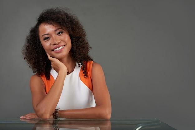 Tiro de cintura de mujer asiática sentada a la mesa sonriendo a la cámara
