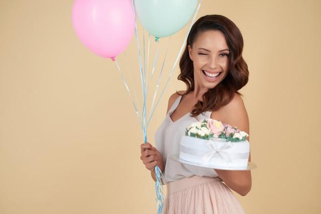 Tiro de cintura de mujer atractiva con un pastel de cumpleaños y globos guiñando un ojo a la cámara