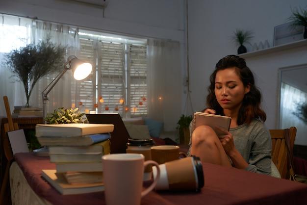 Tiro de cintura de niña sentada en su escritorio con pila de libros de texto escrito
