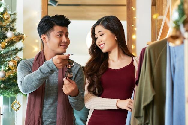 Tiro de la cintura de la pareja asiática de compras mirando las gafas de sol