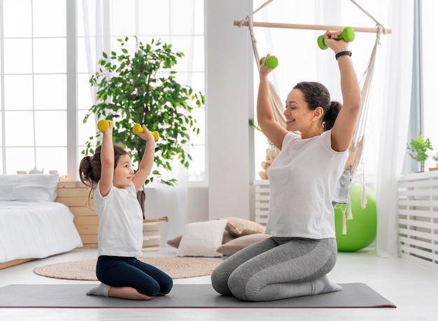 Tiro completo adulto y niño sosteniendo pesas
