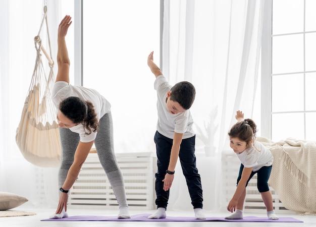 Tiro completo para adultos y niños haciendo deporte.