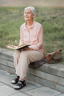 Tiro completo anciana sosteniendo libro