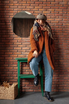 Tiro completo chica de moda con abrigo posando
