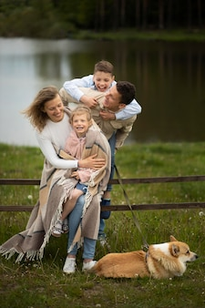 Tiro completo familia feliz y perro al aire libre
