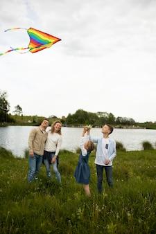 Tiro completo familia feliz volando cometa arco iris
