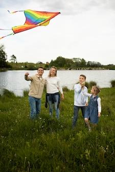 Tiro completo familia feliz volando cometa juntos