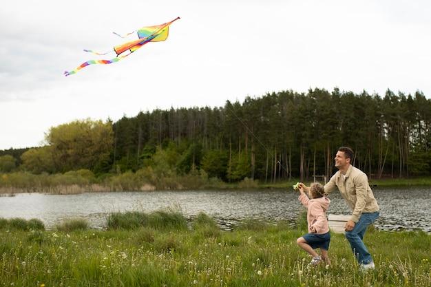 Tiro completo familia feliz volando cometa en la naturaleza