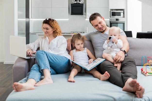 Tiro completo familia sonriente en el sofá