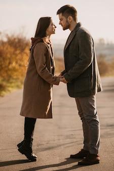 Tiro completo feliz pareja cogidos de la mano