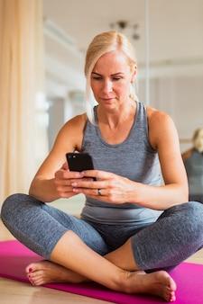 Tiro completo fit mujer revisando su teléfono
