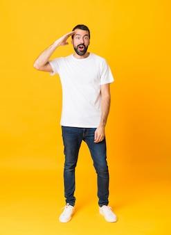 El tiro completo del hombre con barba sobre amarillo aislado acaba de darse cuenta de algo y tiene la intención de encontrar la solución